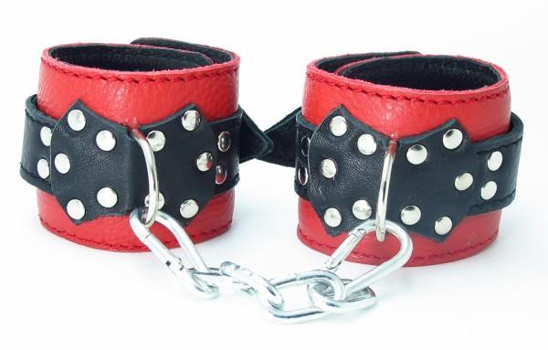 Красные наручники с чёрными проклёпанными ремешками с пряжкой